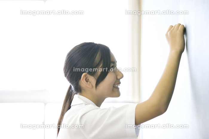 黒板に解答を書く女子中学生の販売画像