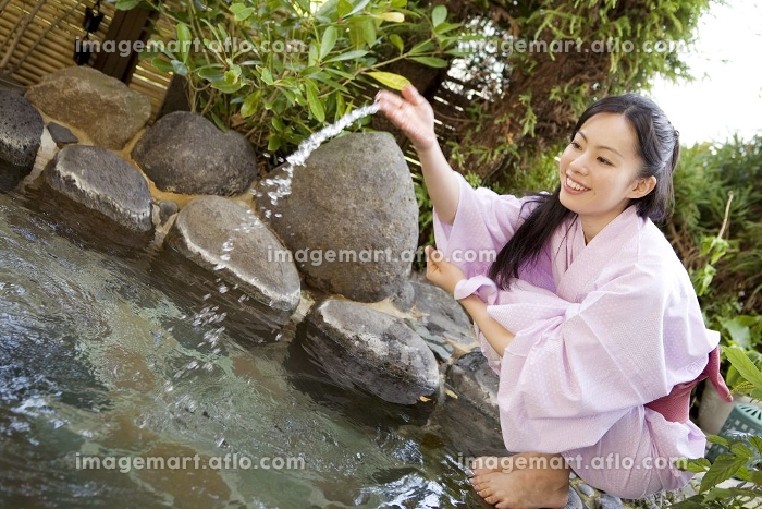 露天風呂の湯加減をみる女性