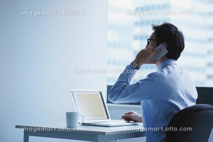 オフィスでデスクワークをするビジネスマンの販売画像