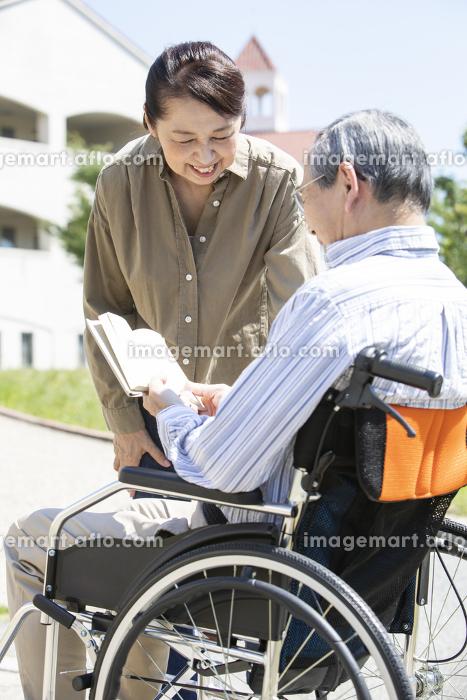 本を読む車椅子に乗った男性と女性の販売画像
