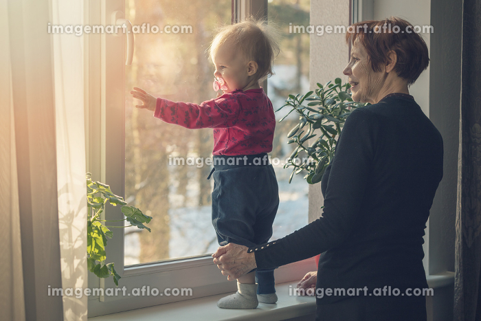 child and nanny spending time together at home looking through the window