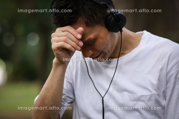 音楽を聴きながら泣く男性の販売画像