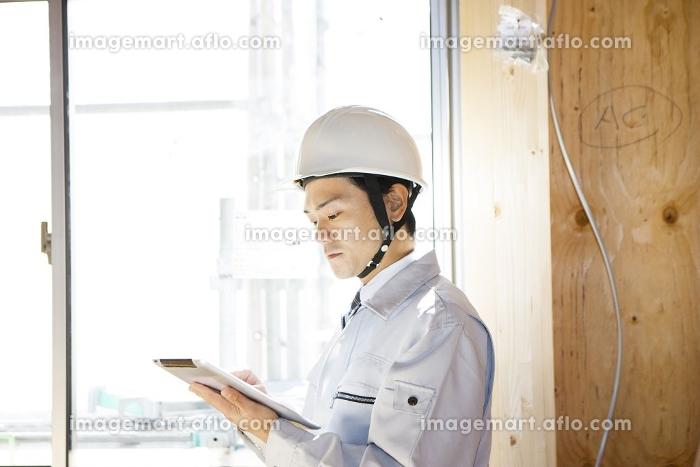 タブレットで建築中の家の中をチェックする現場監督の販売画像