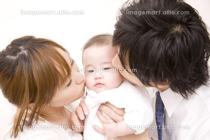 両親にキスをされる赤ちゃんの販売画像