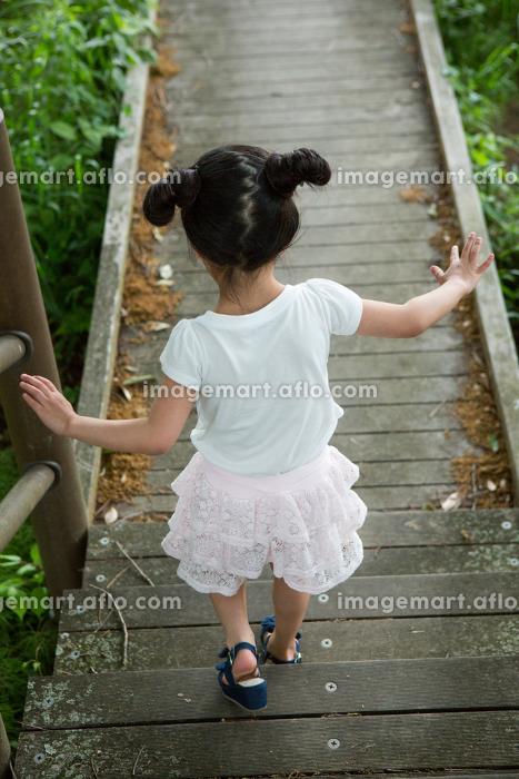 木の道を歩く少女