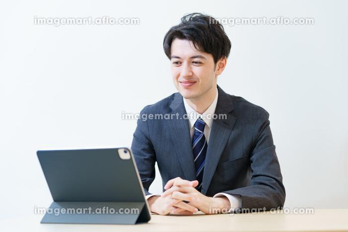 リラックスした表情でオンライン面接・会議・打ち合わせに臨むスーツ姿の男性の販売画像