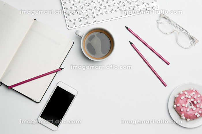 Office desk table with computer, supplies, phone and coffee cup.の販売画像