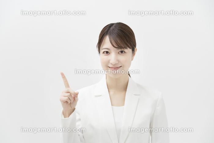 指を上げるポーズをする、白いスーツを着た女性の販売画像