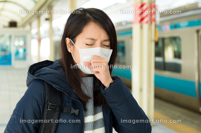 Woman wearing face mask in train stationの販売画像