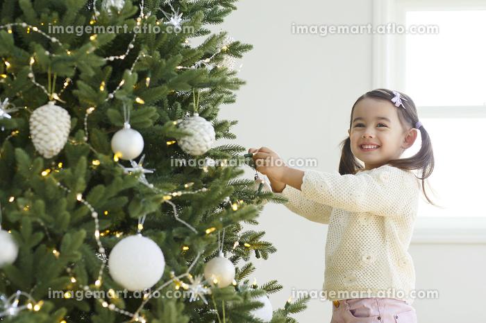 クリスマスツリーに飾り付けをする小さな女の子の販売画像