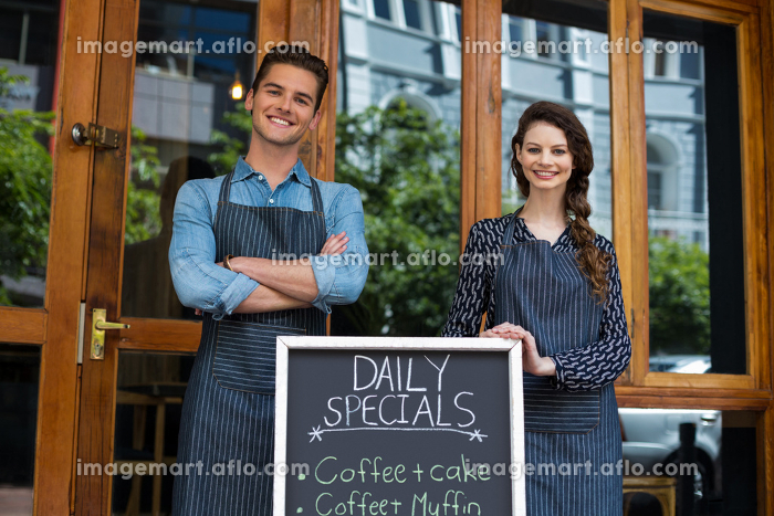 Waiter and waitress standing with menu board outside the cafeの販売画像