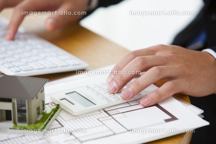 電卓に金額を打ち込む男性ビジネスマンの販売画像