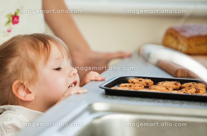 Smiling young girl looking at cookie in kitchenの販売画像