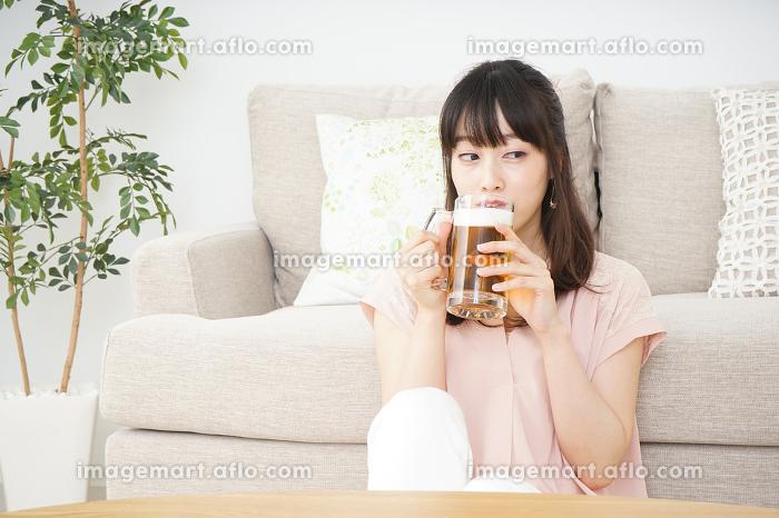 自宅でビールを飲む若い女性の販売画像