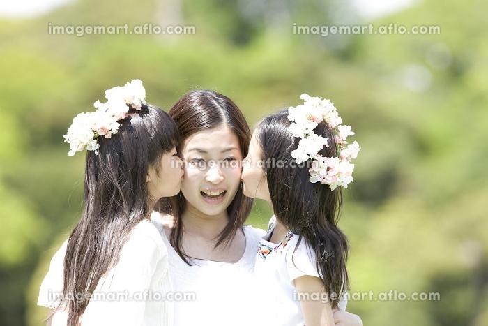 お姉さんの頬にキスする2人の女の子の販売画像