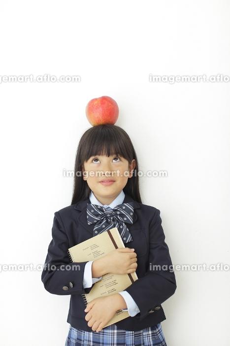 頭にりんごをのせた制服姿の女の子の販売画像