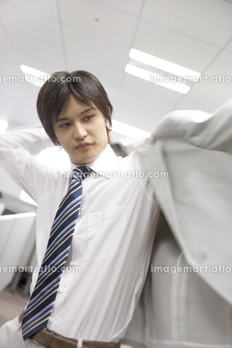 スーツの上着を着るビジネスマンの販売画像
