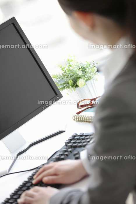 デスクワークをするビジネスウーマンの後姿の販売画像