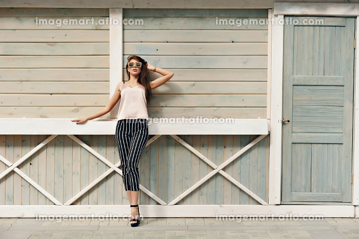 Beautiful woman, wearing dark glasses, against the background of a tree wall. The model wears stylish clothes, beige knitwear and black breeches in a white stripe. Hair develops in the wind. Women's fashion. Urban lifestyleの販売画像