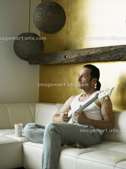Man playing guitar on couchの販売画像