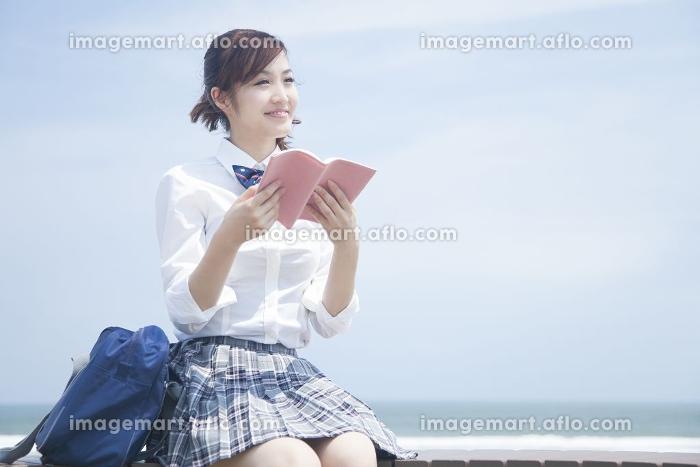 海辺で読書する女子高校生の販売画像