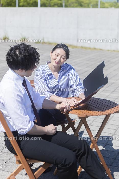 屋外で打ち合わせする男女の販売画像