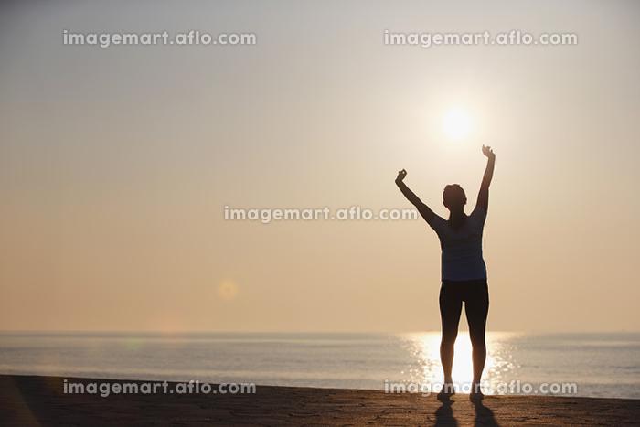 太陽とストレッチをする女性