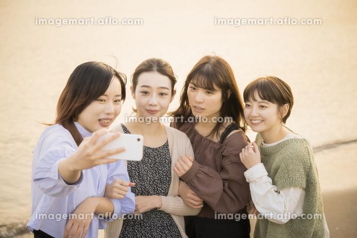 スマートフォンで記念撮影をする女性4人の販売画像