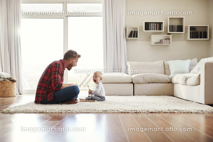 Young father and son playing together in their sitting roomの販売画像