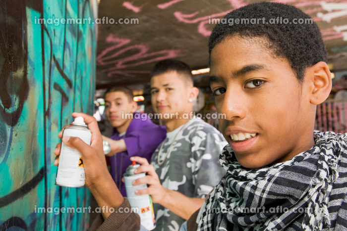 Teenage gang doing graffiti on a wallの販売画像