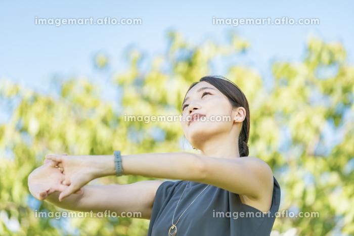 緑の中でリラックスする若い女性の販売画像