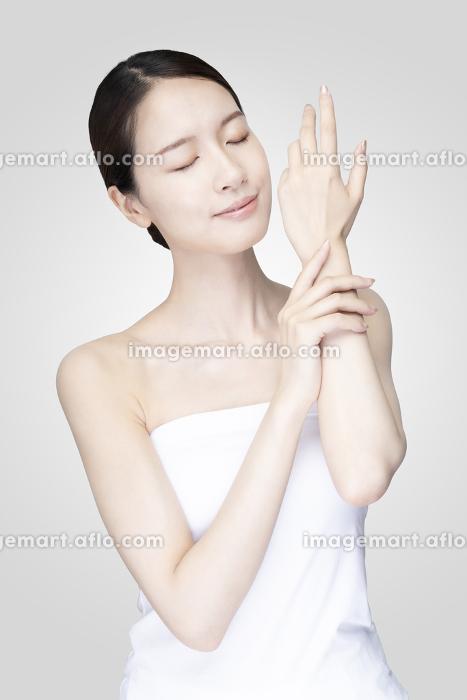 リラックスした表情で顔を触る若い女性の販売画像