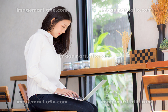Beautiful asian young woman working online on laptop sitting atの販売画像
