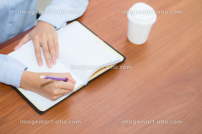 closeup woman hand writing on notebook on wooden table, girl wor