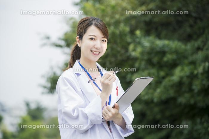 カルテとペンを持つ医療従事者の販売画像