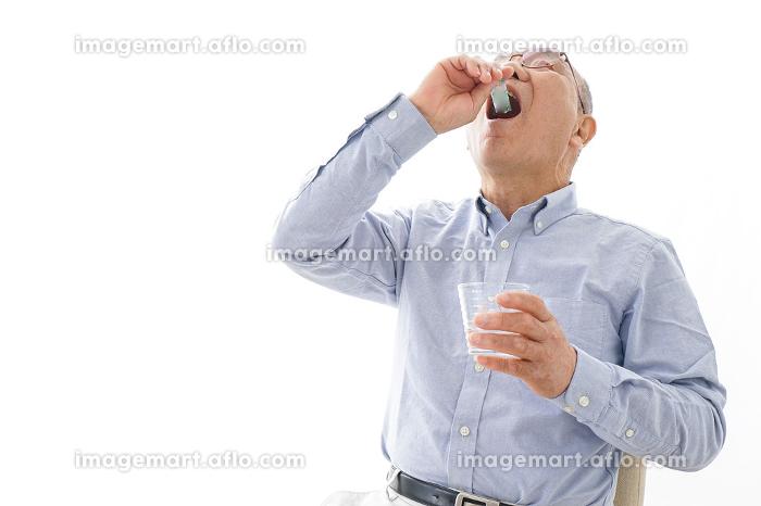 薬を飲む高齢男性の販売画像