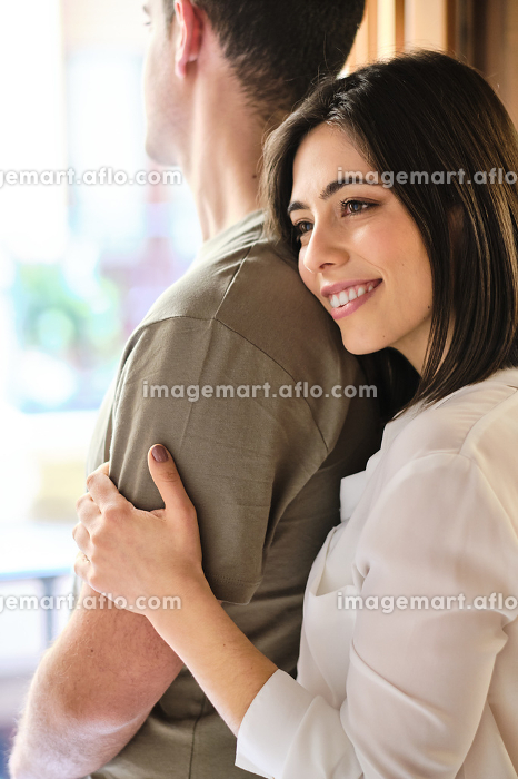 Young couple embracing against window at homeの販売画像