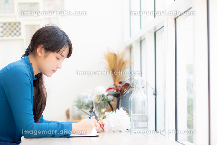 Beautiful portrait young asia woman writer writing on notebook oの販売画像