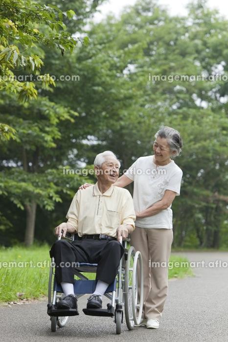 車椅子で散歩をするシニア夫婦の販売画像