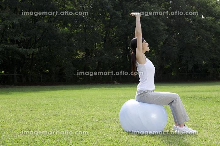 バランスボールを使ってストレッチする女性の販売画像