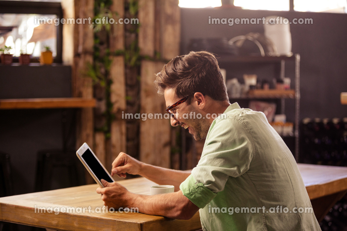 Profile view of hipster man using tablet