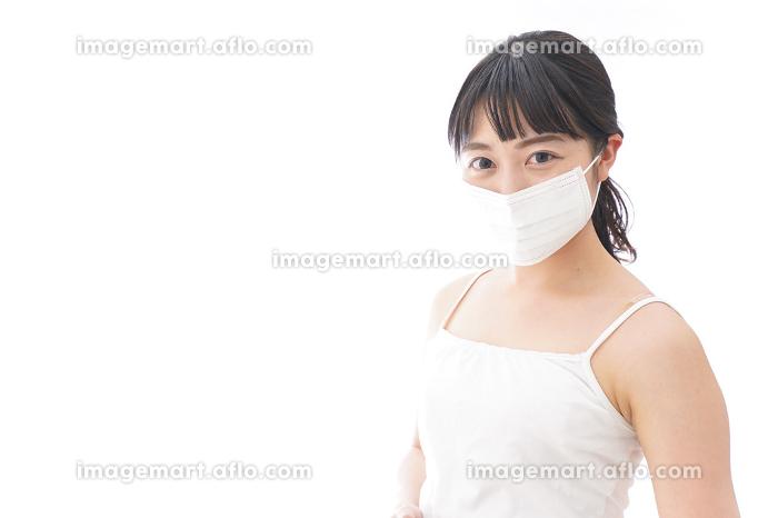 花粉症・風邪・インフルエンザに苦しみマスクをする若い女性の販売画像