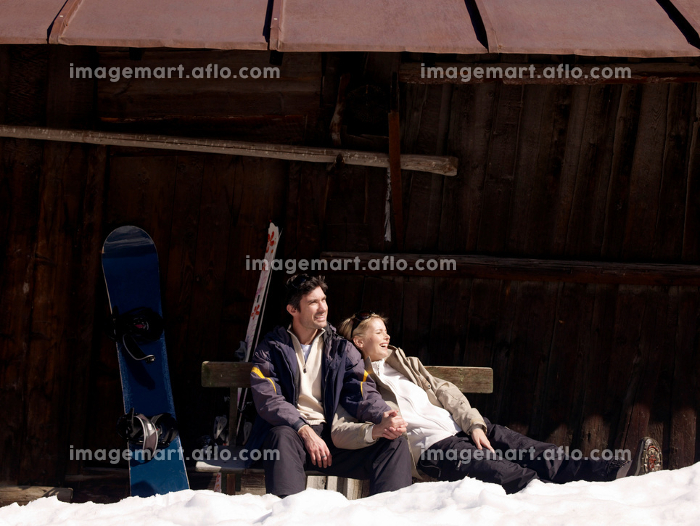 woman and man relaxing by hut
