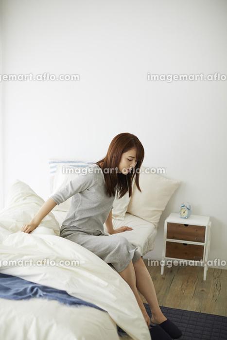 ベッドから起き上がる日本人女性の販売画像