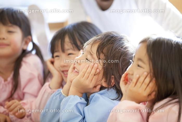頬杖をついて微笑む幼稚園児の販売画像