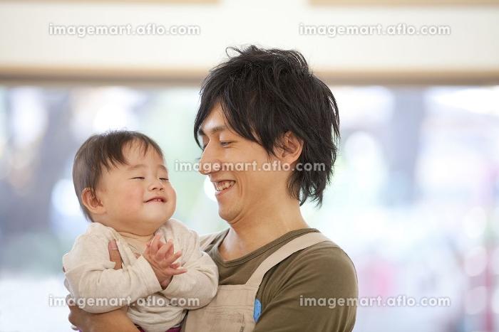 保育士に抱っこされる保育園男児の販売画像