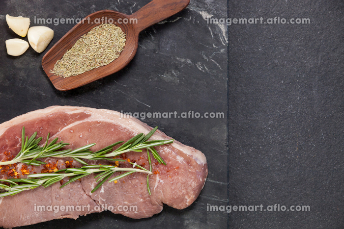 Sirloin chop, garlic and spices on black slate plateの販売画像