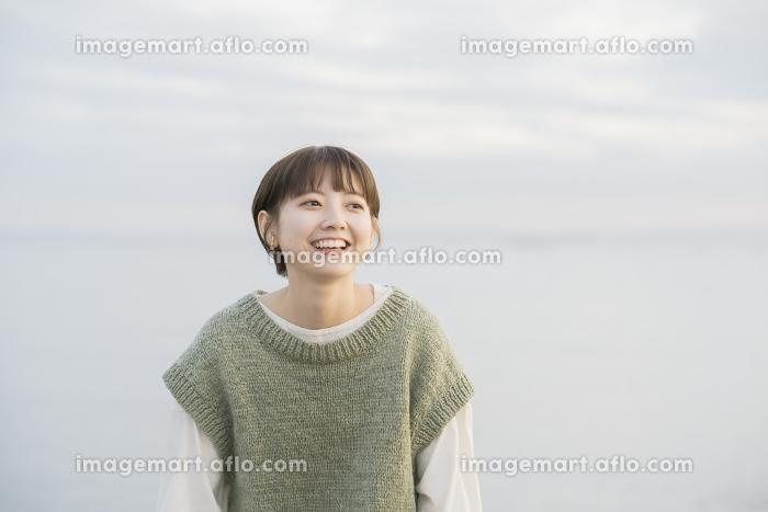 夕方、海をバックに撮影された若い女性のポートレートの販売画像