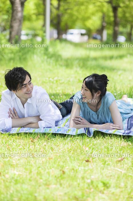 公園で談笑するカップルの販売画像