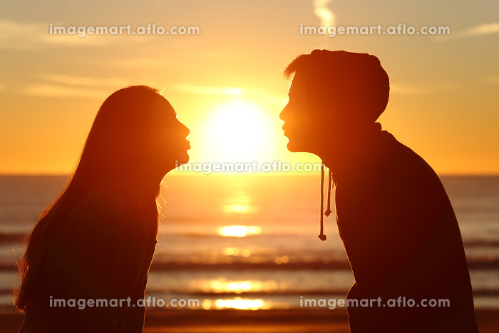 Couple kissing sun with love at sunsetの販売画像